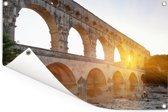 Oranje zon schijnt door een gat van de Pont du Gard Tuinposter 180x120 cm - Tuindoek / Buitencanvas / Schilderijen voor buiten (tuin decoratie) XXL / Groot formaat!