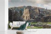 Fotobehang vinyl - Zonnestralen over de Tintern Abbey in Wales breedte 390 cm x hoogte 260 cm - Foto print op behang (in 7 formaten beschikbaar)