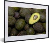 Foto in lijst - Eenzame avocado helft op een hoopje fotolijst zwart met witte passe-partout klein 40x30 cm - Poster in lijst (Wanddecoratie woonkamer / slaapkamer)