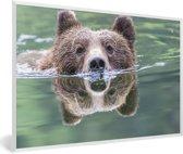 Foto in lijst - Een Grizzlybeer zwemt in het blauwe water fotolijst wit 60x40 cm - Poster in lijst (Wanddecoratie woonkamer / slaapkamer)