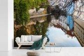 Fotobehang vinyl - Het stadszicht van Praag weerspiegelt in de prachtige wateren van de rivier de Moldau breedte 390 cm x hoogte 260 cm - Foto print op behang (in 7 formaten beschikbaar)