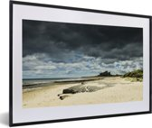 Foto in lijst - Dreigende lucht boven het Kasteel van Bamburgh fotolijst zwart met witte passe-partout 60x40 cm - Poster in lijst (Wanddecoratie woonkamer / slaapkamer)