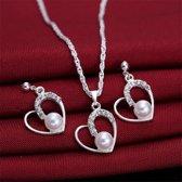 Fashionidea – mooie zilverkleurige ketting met hartjes hanger voorzien van witte kunstparel en glimmende zirkonias,  aangevuld met bijpassende oorbellen