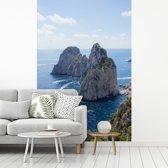 Fotobehang vinyl - Mooie rotsformatie in de zee van Capri in Italië breedte 215 cm x hoogte 320 cm - Foto print op behang (in 7 formaten beschikbaar)