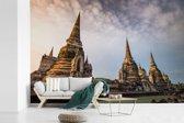Fotobehang vinyl - Mooie lucht boven de historische tempels in Ayutthaya breedte 450 cm x hoogte 300 cm - Foto print op behang (in 7 formaten beschikbaar)