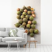Fotobehang vinyl - Groepje groene macadamianoten in de schil breedte 150 cm x hoogte 220 cm - Foto print op behang (in 7 formaten beschikbaar)