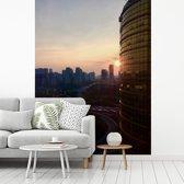 Fotobehang vinyl - Mooie zonsondergang langs een hoog gebouw in Nanning breedte 225 cm x hoogte 300 cm - Foto print op behang (in 7 formaten beschikbaar)
