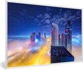 Foto in lijst - De hoogbouw Dubai steekt in de nacht boven de wolken uit fotolijst wit 60x40 cm - Poster in lijst (Wanddecoratie woonkamer / slaapkamer)