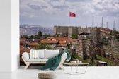 Fotobehang vinyl - De Turkse vlag wappert hoog boven de huizen van Ankara breedte 450 cm x hoogte 300 cm - Foto print op behang (in 7 formaten beschikbaar)