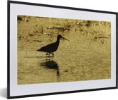 Foto in lijst - Een silhouet van een Grutto in het zand fotolijst zwart met witte passe-partout 60x40 cm - Poster in lijst (Wanddecoratie woonkamer / slaapkamer)