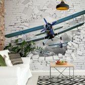 Fotobehang 3D Plane Bursting Through Brick Wall | VEXXL - 312cm x 219cm | 130gr/m2 Vlies