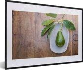 Foto in lijst - Verse avocado op een plaat fotolijst zwart met witte passe-partout 60x40 cm - Poster in lijst (Wanddecoratie woonkamer / slaapkamer)
