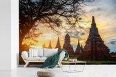 Fotobehang vinyl - De zon schijnt tussen de tempels door in Ayutthaya breedte 540 cm x hoogte 360 cm - Foto print op behang (in 7 formaten beschikbaar)