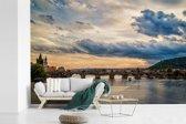 Fotobehang vinyl - Een wolkenlucht boven de Karelsbrug in Praag breedte 450 cm x hoogte 300 cm - Foto print op behang (in 7 formaten beschikbaar)
