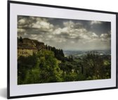 Foto in lijst - Wolken over de Toscaanse heuvels in de Italiaanse ommuurde stad San Gimignano fotolijst zwart met witte passe-partout 60x40 cm - Poster in lijst (Wanddecoratie woonkamer / slaapkamer)