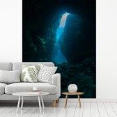 Fotobehang vinyl - Een grot bij Grand Cayman met doorschijnende zonnestralen breedte 235 cm x hoogte 320 cm - Foto print op behang (in 7 formaten beschikbaar)