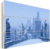 Een besneeuwde Karelsbrug tijdens een koude winter in Tsjechië Vurenhout met planken 60x40 cm - Foto print op Hout (Wanddecoratie)