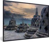 Foto in lijst - Donkere wolken boven de Borobudur tempel fotolijst zwart 60x40 cm - Poster in lijst (Wanddecoratie woonkamer / slaapkamer)