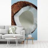 Fotobehang vinyl - Kokosnoot met kokoswater tegen lichtblauwe achtergrond breedte 140 cm x hoogte 220 cm - Foto print op behang (in 7 formaten beschikbaar)