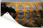 Een geel kleurige Pont du Gard door de laagstaande zon Tuinposter 180x120 cm - Tuindoek / Buitencanvas / Schilderijen voor buiten (tuin decoratie) XXL / Groot formaat!