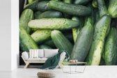 Fotobehang vinyl - Een stapel volle komkommers breedte 600 cm x hoogte 400 cm - Foto print op behang (in 7 formaten beschikbaar)