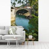 Fotobehang vinyl - Foto vanuit de planten van de Stari Most brug breedte 175 cm x hoogte 260 cm - Foto print op behang (in 7 formaten beschikbaar)