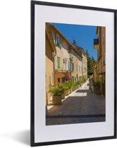 Foto in lijst - Gezellig straatje in het Franse Saint-Tropez fotolijst zwart met witte passe-partout 40x60 cm - Poster in lijst (Wanddecoratie woonkamer / slaapkamer)