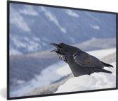 Foto in lijst - Een raaf kraait in een winters landschap fotolijst zwart 60x40 cm - Poster in lijst (Wanddecoratie woonkamer / slaapkamer)