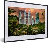 Foto in lijst - De Petronas Towers tussen de bladeren fotolijst zwart met witte passe-partout klein 40x30 cm - Poster in lijst (Wanddecoratie woonkamer / slaapkamer)