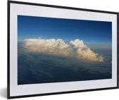 Foto in lijst - Luchtfoto van een wolkenbed onder een helderblauwe lucht fotolijst zwart met witte passe-partout 60x40 cm - Poster in lijst (Wanddecoratie woonkamer / slaapkamer)