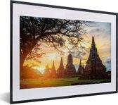 Foto in lijst - De zon schijnt tussen de tempels door in Ayutthaya fotolijst zwart met witte passe-partout klein 40x30 cm - Poster in lijst (Wanddecoratie woonkamer / slaapkamer)