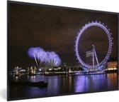 Foto in lijst - Paars vuurwerk en een paarse London Eye in de avond in Londen fotolijst zwart 60x40 cm - Poster in lijst (Wanddecoratie woonkamer / slaapkamer)