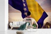 Fotobehang vinyl - Voetballer staat voor de vlag van Bosnië en Herzegovina breedte 360 cm x hoogte 240 cm - Foto print op behang (in 7 formaten beschikbaar)