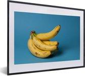 Foto in lijst - Oudere tros bananen op donkerblauwe achtergrond fotolijst zwart met witte passe-partout klein 40x30 cm - Poster in lijst (Wanddecoratie woonkamer / slaapkamer)