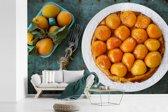 Fotobehang vinyl - Bord gevuld met abrikozen op een blauwe tafel breedte 540 cm x hoogte 360 cm - Foto print op behang (in 7 formaten beschikbaar)