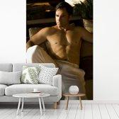 Fotobehang vinyl - Een gespierde man met een witte broek breedte 150 cm x hoogte 220 cm - Foto print op behang (in 7 formaten beschikbaar)