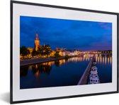 Foto in lijst - Verlichting in de avond in het Nederlandse Maastricht fotolijst zwart met witte passe-partout klein 40x30 cm - Poster in lijst (Wanddecoratie woonkamer / slaapkamer)