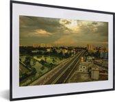 Foto in lijst - Gele tinten in de lucht boven Dhaka fotolijst zwart met witte passe-partout klein 40x30 cm - Poster in lijst (Wanddecoratie woonkamer / slaapkamer)