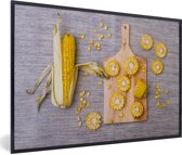 Foto in lijst - Gesneden maïskolven op een hakbord fotolijst zwart 60x40 cm - Poster in lijst (Wanddecoratie woonkamer / slaapkamer)