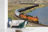 Fotobehang vinyl - Een oranje gekleurde trein breedte 450 cm x hoogte 300 cm - Foto print op behang (in 7 formaten beschikbaar)