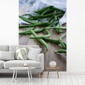 Fotobehang vinyl - Stapel van groene pronkbonen op een houten ondergrond breedte 180 cm x hoogte 270 cm - Foto print op behang (in 7 formaten beschikbaar)