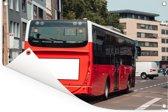 Een rood gekleurde bus in de stad Tuinposter 90x60 cm - Tuindoek / Buitencanvas / Schilderijen voor buiten (tuin decoratie)