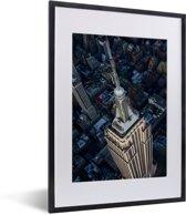 Foto in lijst - Schuin bovenaanzicht van het Empire State Building in Amerika fotolijst zwart met witte passe-partout klein 30x40 cm - Poster in lijst (Wanddecoratie woonkamer / slaapkamer)