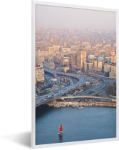 Foto in lijst - Rode zeilboot vaart over de Nijl in de Egyptische stad Caïro fotolijst wit 40x60 cm - Poster in lijst (Wanddecoratie woonkamer / slaapkamer)