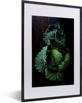 Foto in lijst - Donkergroene savooiekool tegen een donkere achtergrond fotolijst zwart met witte passe-partout 40x60 cm - Poster in lijst (Wanddecoratie woonkamer / slaapkamer)