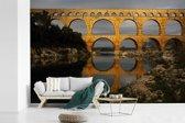 Fotobehang vinyl - Een geel kleurige Pont du Gard door de laagstaande zon breedte 420 cm x hoogte 280 cm - Foto print op behang (in 7 formaten beschikbaar)