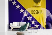 Fotobehang vinyl - Voetballer achter de vlag van Bosnië en Herzegovina breedte 330 cm x hoogte 220 cm - Foto print op behang (in 7 formaten beschikbaar)