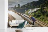 Fotobehang vinyl - Chinese boer in de Rijstterrassen van Lóngjĭ in China breedte 360 cm x hoogte 240 cm - Foto print op behang (in 7 formaten beschikbaar)