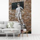 Fotobehang vinyl - Het standbeeld van David van Michelangelo voor een stenen muur breedte 235 cm x hoogte 350 cm - Foto print op behang (in 7 formaten beschikbaar)
