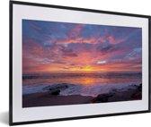 Foto in lijst - Een kleurrijke zonsondergang bij de zee fotolijst zwart met witte passe-partout 60x40 cm - Poster in lijst (Wanddecoratie woonkamer / slaapkamer)